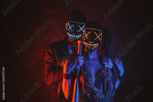 Cuadros en Lienzo Man and woman in masks are posing for photographer with baseball bat in red and blue lights