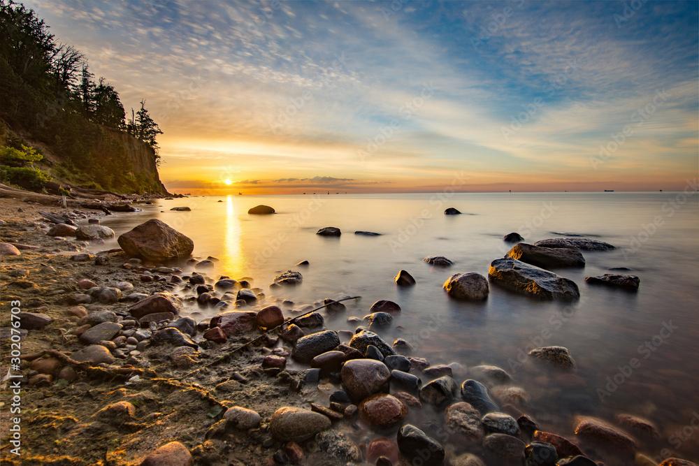 Fototapeta Wschód słońca na plaży w Gdyni z klifem Orłowskim w tle, Morze Bałtyckie, Polska