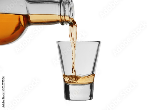 Strong alcoholic drink pour from a bottle into a wineglass isolated on a white b Wallpaper Mural