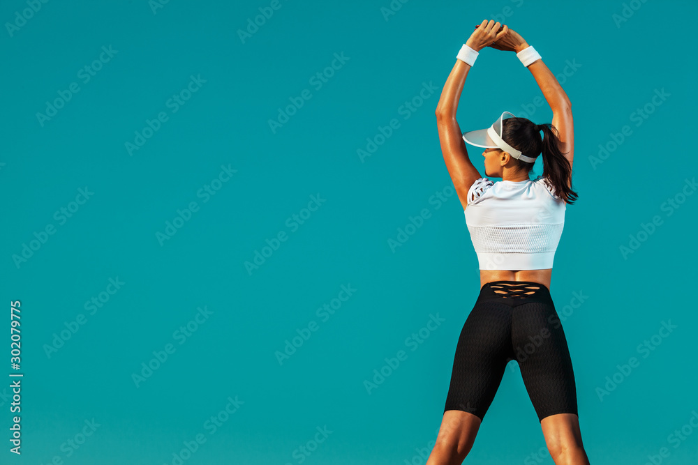 Fototapeta Sporty and fit young woman athlete doing yoga training on the sky background. The concept of a healthy lifestyle and sport. Individual sports recreation.