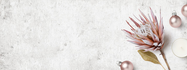 bright feminine winter / Christmas banner or header with dry Protea flower, small pastel pink xmas ornaments and a candle on a white wooden board - flat lay / top view
