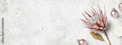 Fototapeta bright feminine winter / Christmas banner or header with dry Protea flower, small pastel pink xmas ornaments and a candle on a white wooden board - flat lay / top view obraz