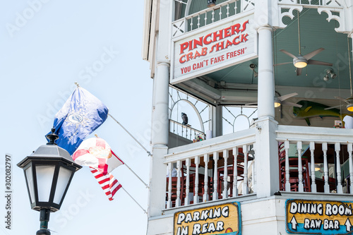 Key West, USA - May 1, 2018: Entrance exterior of Pincher's Crab Shack restaurant seafood dining building balcomy. sign in Florida urban city travel, sunny day, blue sky, chairs, tables