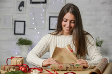 Happy Smiling Woman Wrapping Christmas Presents, Winter Holidays, Gifting Season Concept