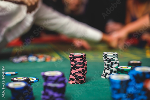 A close-up vibrant image of multicolored casino table with roulette in motion, with casino chips Wallpaper Mural