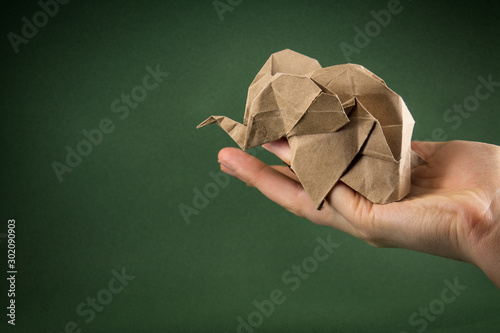 origami baby elephant craft paper on a green background on the hand, the concept Wallpaper Mural
