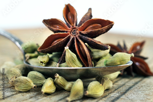 Fototapeta traditional spices. cardamom and anise stars in a spoon on a wooden table. close up.  obraz