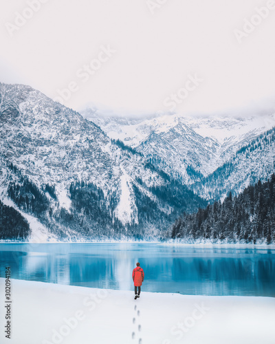 Tuinposter Wit Person at Lake Plansee in Austria during Winter