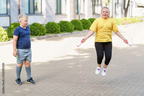 Boy looking at a girl jumping with a rope Fototapete