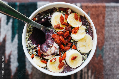 Silver spoon scooping out bite of acai bowl topped with dried goji berries, seed Wallpaper Mural