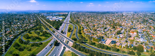 Fotomural  Scenic aerial panorama of highway interchange in greater Melbourne suburbs on su