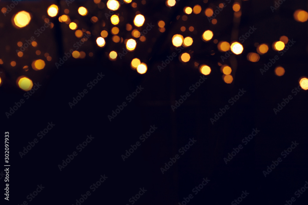 Fototapeta winter holidays Christmas post card concept wallpaper picture of golden bokeh from garland illumination on black background empty copy space for your text here