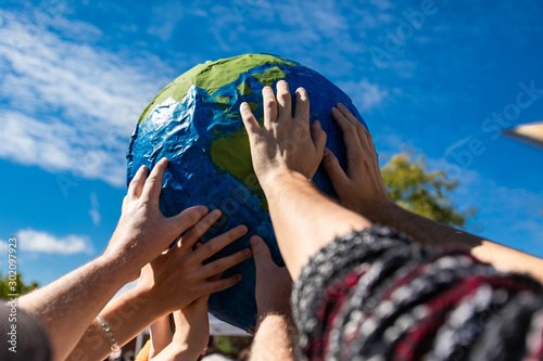 group of hands holding and protecting terrestrial globe as a symbol of environmentalism Canvas Print