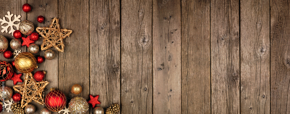 Fototapeta Red and gold Christmas ornament corner border banner. Above view on a rustic wood background.