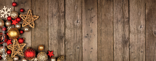 Poster Countryside Red and gold Christmas ornament corner border banner. Above view on a rustic wood background.