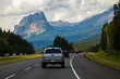 cars, pickups and SUVs are traveling accross the canadian rockies on a 4 lane highway. High mountain peaks and dense clouds in the background
