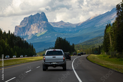 Cuadros en Lienzo  cars, pickups and SUVs are traveling accross the canadian rockies on a 4 lane highway