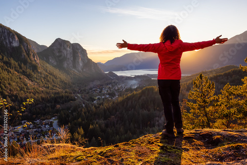 Fotomural  Adventurous Girl Hiking in the mountains during a sunny Autumn Sunset
