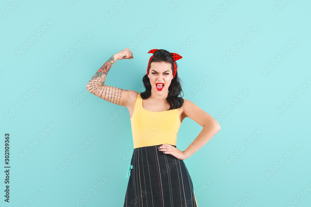 Fototapety, obrazy: Portrait of strong tattooed pin-up woman on color background