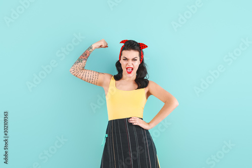 Photographie  Portrait of strong tattooed pin-up woman on color background
