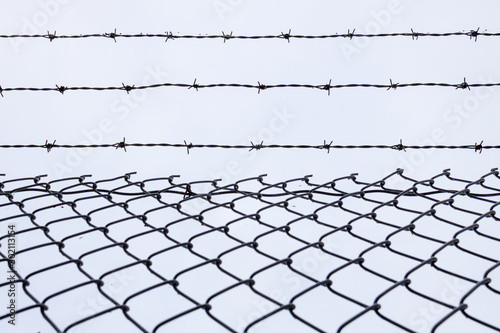 Chainlink fence with three strands of barbed wire on top Canvas Print