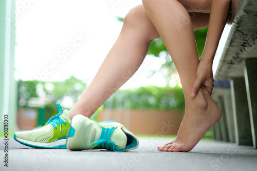 Garden Poster Spa Foot Pain Leg of woman which runner athletic by running shoes sitting on grass in the park holding he feet and stretch the muscles in morning sunlight .Health care and spa concept
