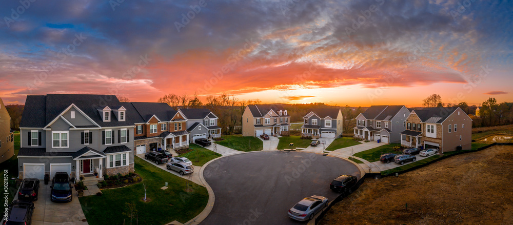 Aerial view of cul de sac neighborhood suburban street with luxury houses in upper middle class American real estate development in the USA with stunning red, yellow, orange sunset color sky