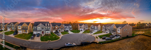 Obraz Aerial view of new construction cul-de-sac street with luxury houses in a Maryland upper middle class neighborhood American real estate development in the USA with stunning sunset orange color sky - fototapety do salonu