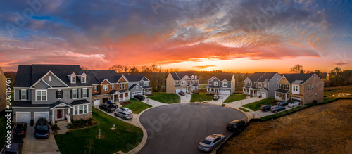 Obraz Aerial view of new construction street with luxury houses in cul-de-sac upper middle class neighborhood American real estate development in the USA with stunning red, yellow, orange sunset color sky	 - fototapety do salonu