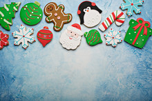 Christmas Sugar And Gingerbread Cookies Decorated With Royal Icing On A Light Blue Surface