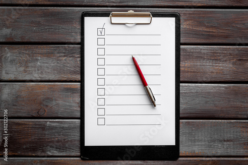 Fototapeta Empty check list ready to fill on dark wooden background top view obraz