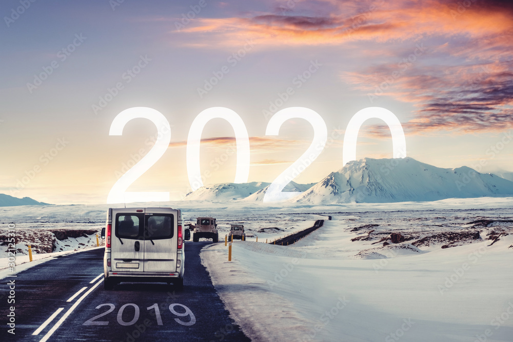 Fototapeta New year and new achievements concept. Group of car driving on the road heading to 2020 with 2019 on the road