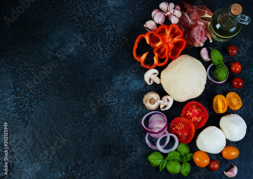 The ingredients of a pizza lay on a black concrete background Fototapete