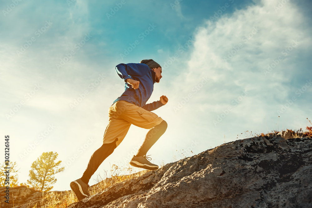 Fototapeta Skyrunner skyrunning crosscountry concept with young athlete on big rock