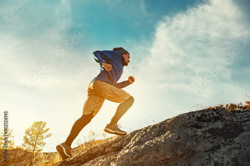 Leinwand Poster  Skyrunner skyrunning crosscountry concept with young athlete on big rock