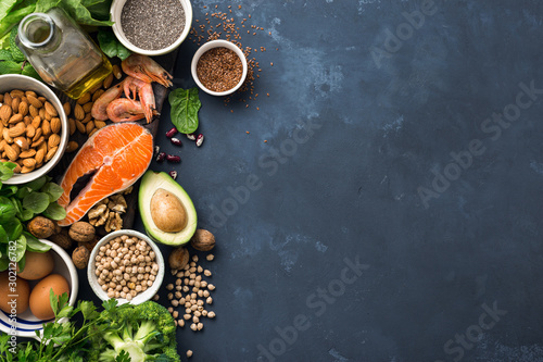 Fototapeta Food sources of omega 3 and healthy fats on dark background top view. Copy Space. Vegetables, seafood, nut and seed obraz