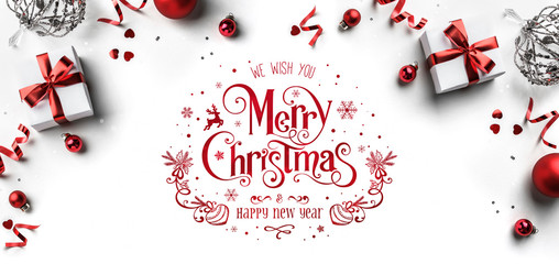 Merry Christmas and New Year text on white background with gift boxes, ribbons, red decoration, bokeh, sparkles and confetti. Xmas greeting card, bokeh, light. Flat lay, top view