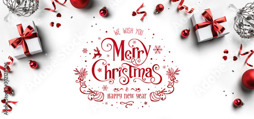 Cuadros en Lienzo  Merry Christmas and New Year text on white background with gift boxes, ribbons, red decoration, bokeh, sparkles and confetti