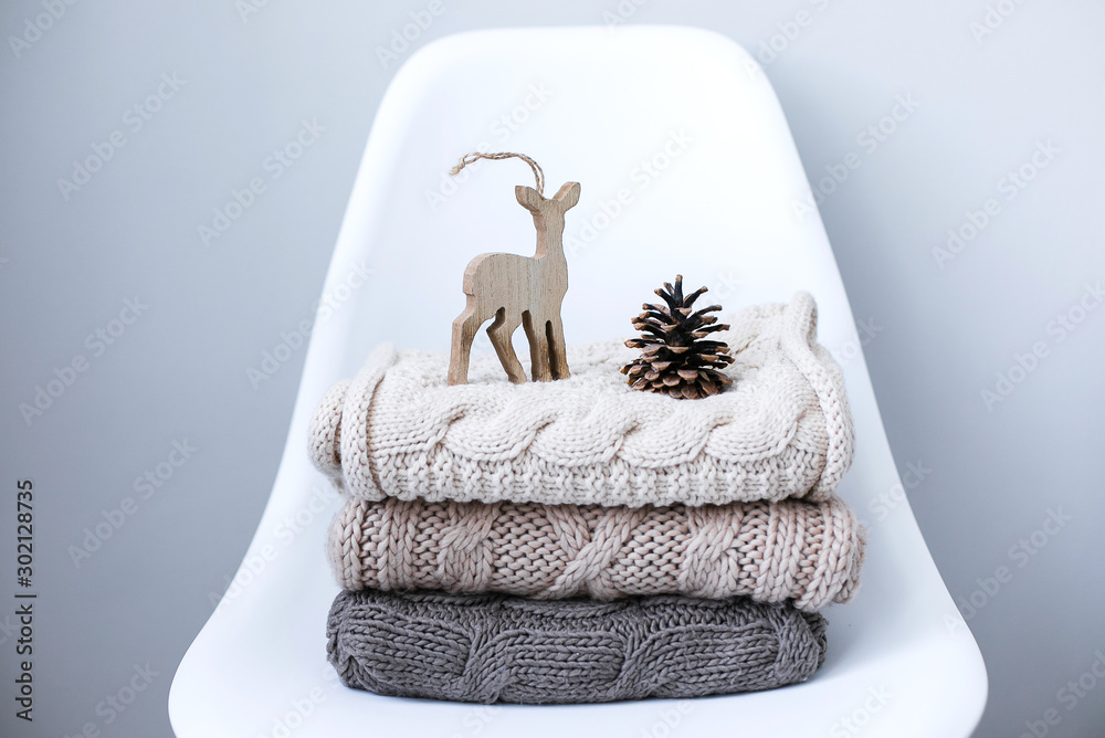 Fototapety, obrazy: A stack of knitted sweaters on chair in Interior of the living room