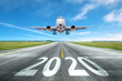 canvas print picture - The inscription on the runway 2020 surface of the airport runway with take off aircraft. Concept of travel in the new year, holidays.
