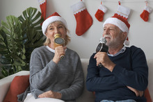 Senior Elderly Caucasian Old Man And Woman Happy To Sing A Song Together In Living Room That Decorated With Christmas Tree For Christmas Festival Day, Retirement Lovely Lifestyle Concept
