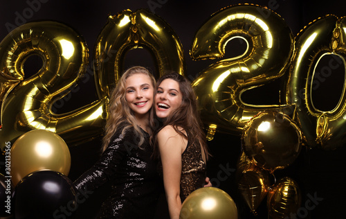 Two happy girls in shiny dresses posing while standing with gold colored 2020 number balloons on black background Wallpaper Mural