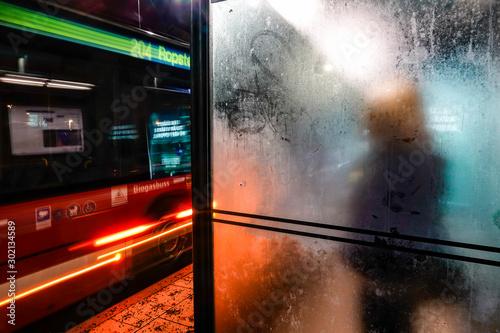 Obraz Stockholm, Sweden A woman waits alone at a bus stop in Lidingo. - fototapety do salonu