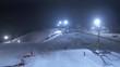 Drohnenaufnahme von einem Flutlicht beleuchteten Skigebiet, mit Skilift in einem Schneebedeckten Wald