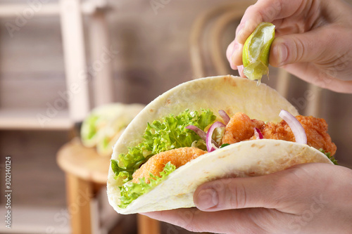 Woman squeezing lime on fish taco indoors, closeup