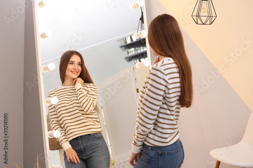 Cuadros en Lienzo Beautiful young woman looking at herself in large mirror indoors