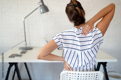 Cuadros en Lienzo Overworked woman with back pain in office with bad posture
