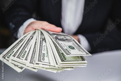 Fotografía  Rich Businessman giving and counting money, us dollars banknotes (USD) bills