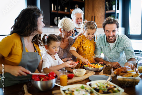 Fototapeta Cheerful family spending good time together while cooking in kitchen obraz