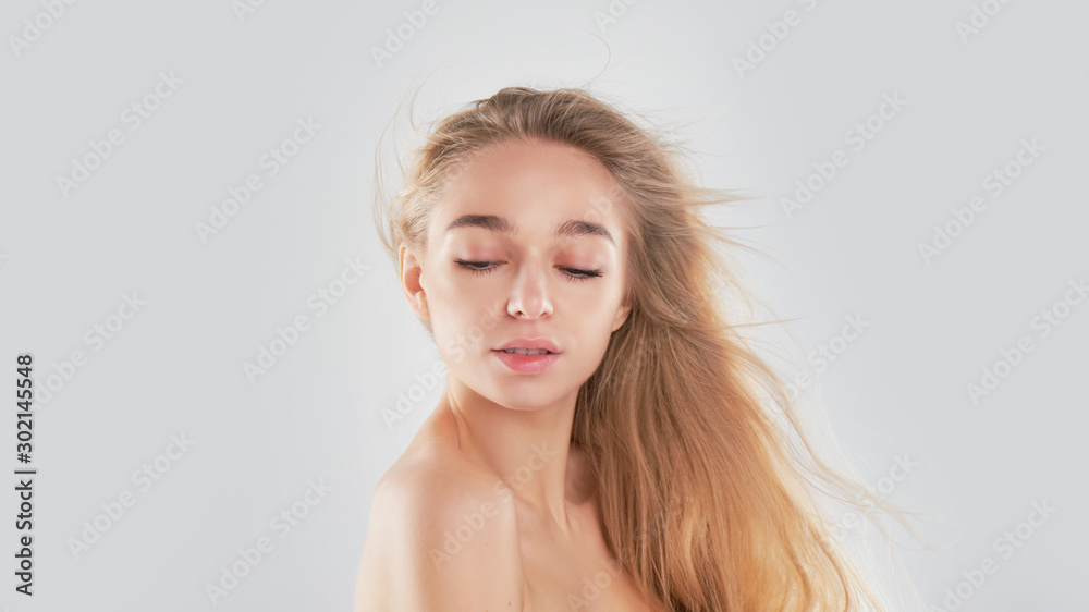 Fototapety, obrazy: Portrait of beauty model with natural nude make up and touching her face. Spa, skincare and wellness. Close up, Gray background, copyspace. hair fluttering in the wind.